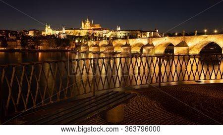 Panoramic View Of Prague Skyline In Night. Charles Bridge Across The River Vltava And Prague Castle
