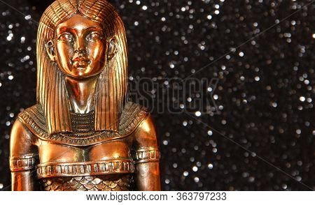 The Egyptian Goddess Isis On A Black Background. A Bronze Egyptian Goddess With A Circle On Her Head