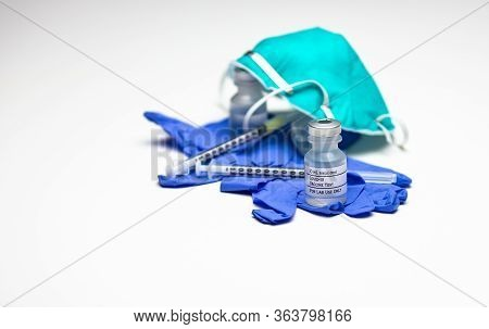 Two Syringes On Top Of Blue Medical Gloves With Two Vials Of Covid-19 Test Vaccine And A Respirator