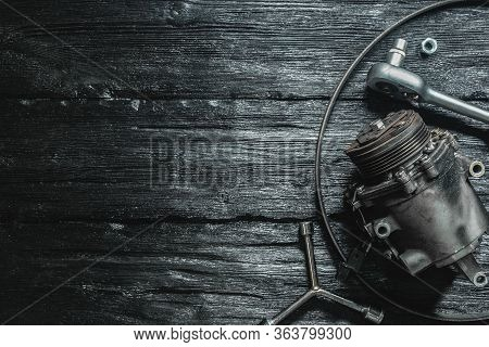 Old Car Air Conditioning Compressor On The Black Wooden Workbench Background.