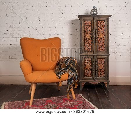 Living Room Corner With French Orange Wingback Armchair, Decorated Wooden Cupboard, On White Bricks