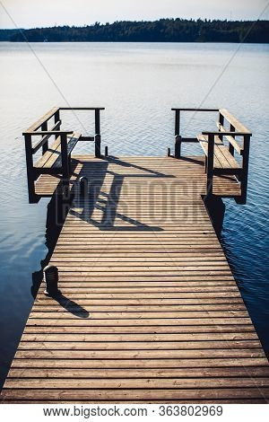 Long Wooden Pier And Beautiful Lake Saimaa, Finland On Warm And Windless Summer Day.