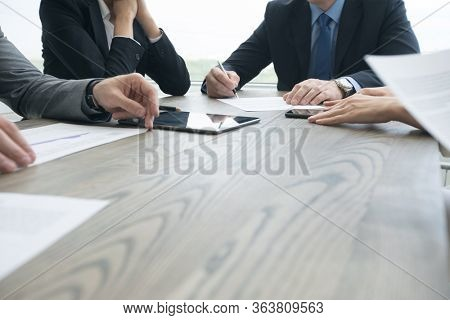 Business people sitting around the desk in a meeting and working with computers and documents