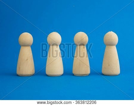 Wooden Figurines Standing On A Blue Background