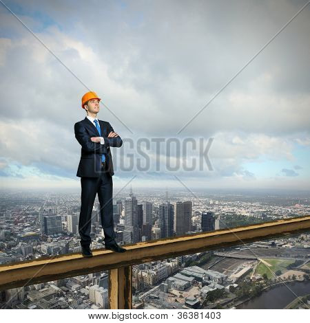 Business man standing high over a cityscape