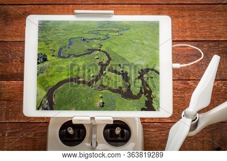 Illinois River meanders through Arapaho National Wildlife Refuge, North Park near Walden, Colorado in early summer, reviewing an aerial image on a digital tablet mounted on a drone radio controller