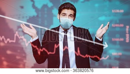 Coronavirus and business. A businessman in a medical mask makes a helpless gesture against the background of a coronavirus and stock charts.