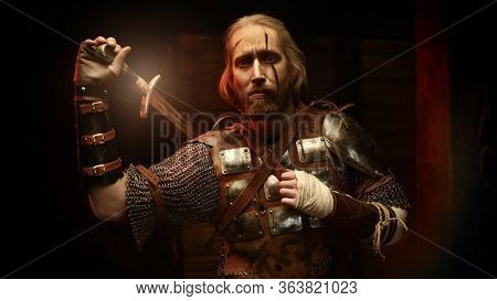 Portrait of a brave medieval warrior in armor with a sword on a dark background. The Witcher man.