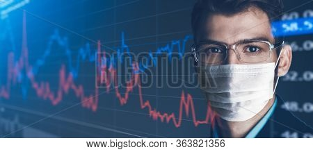 COVID-19 and business. Portrait of a serious confident businessman in a medical mask against the background of stock charts. Copy space.
