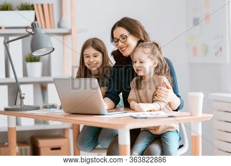 Young mother with children working on the computer. Family at home. Remote work.