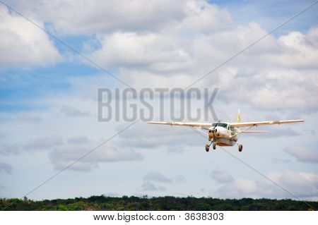 Small white plane with propeller in cloudy sky over jungle poster