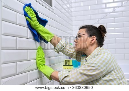 Woman Housewife Doing House Cleaning In Bathroom. Female Polishing Tiled Wall In Bathroom With Micro