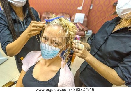 Beautician Hands Making Pearl Braids To A Dreadlocks Woman With A Surgical Mask In An Asian Beauty C