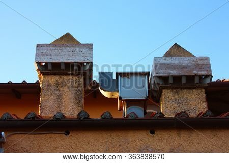 Two Chimneys And A Drain Outlet Pipe On The Cornice Of An Orange Roof Of A Building