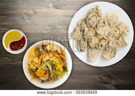 Dumplings On A White Plate On Black Wooden Background .boiled Dumplings With Salad.meat Dumplings To