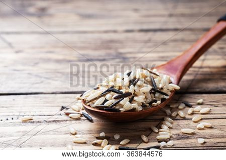 Raw Wild Rice In A Wooden Spoon. Raw Rice Grits On A Wooden Background. Copy Space.
