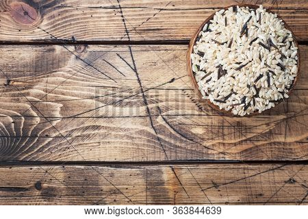 Raw Wild Rice In A Wooden Bowl. Raw Rice Grits On A Wooden Background. Copy Space.