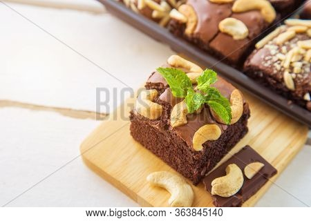 Close Up Chocolate Brownies With Cashew Nut And Peppermint On Wooden Plate On White Wooden Floor Wit