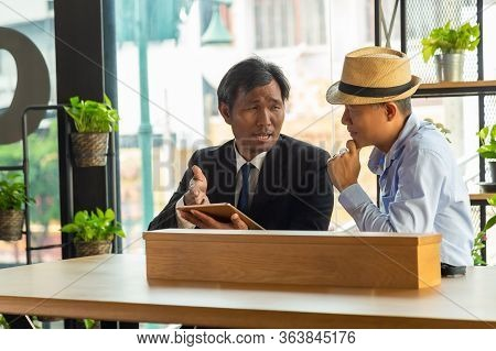 Close Up Two Asian Men Sitting At Cafe Table Discussed The News On The Internet From Tablet Device A