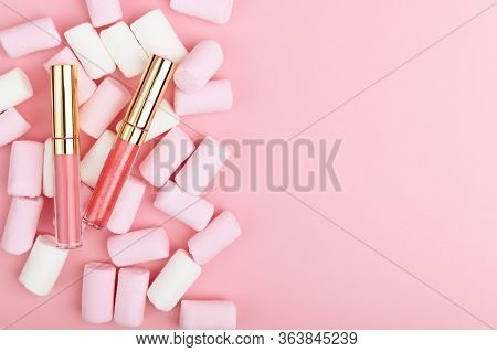 Pink Pastel Lip Gloss On A Background Of Sweets. Decorative Womens Cosmetics Accessory On A Light Ba