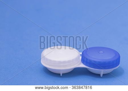 Contact Lens Container On A Blue Background. Storage O Cleaning Contact Lenses For Vision Correction