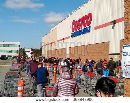 Langley, Canada - April 14, 2020. Shoppers Line Up At Costco, In The Second Half Of The Line, To Get