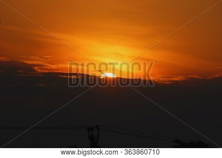 The Sun Sets In Bright Yellow Sky , Sunset Background, Natural Sunset Sunrise Over Field Or Meadow.