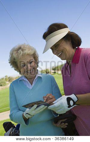 Two female friends writing their golf scores on scorecard