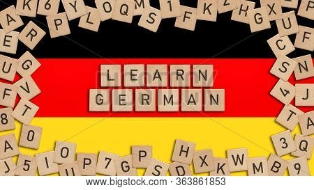 Learn German Word Written With Wooden Tiles Over German Flag. This Image Can Be Used For A Banner Or