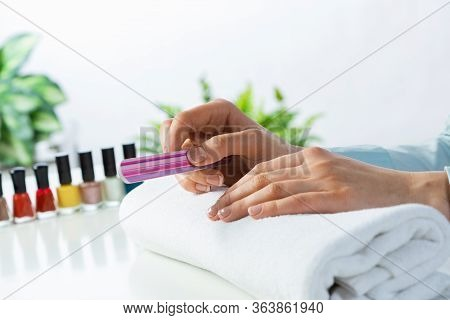 Woman Using Nail File And Create Perfect Nails Shape. Colorful Nail Polish Bottles On Table. Grindin