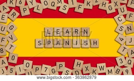 Learn Spanish Word Written With Wooden Tiles Over Spanish Flag. This Image Can Be Used For A Banner