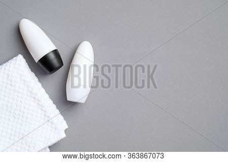 Male Deodorant Perfume Bottles With Towel On Grey Background. Flat Lay, Top View. White Antiperspira
