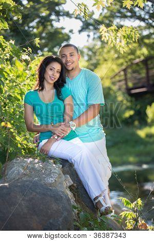 Young Hispanic Couple Engagement Picture Outdoor Portrait Back Lit by River Bank under Bridge
