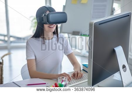 Dark-haired Girl Sitting At The Computer Wearing Vr Headset
