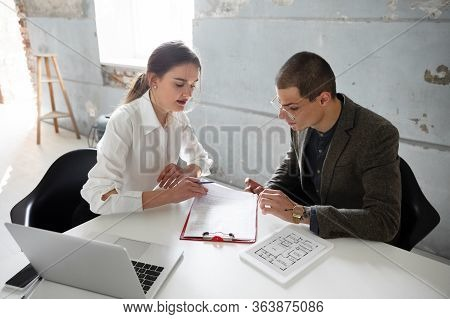 New Solutions. Female Estate Agent Showing New Home To A Young Man After A Discussion On House Plans