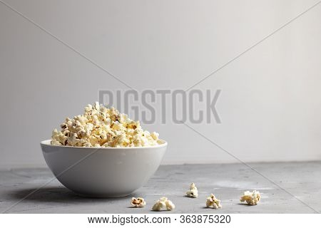 Popcorn In A White Bowl On Grey Table With Few Popcorn Beside Bowl.