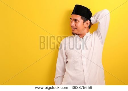 Relaxed Young Asian Muslim Man With A Blissful Smile Leaning Back Look At A Copy Space, Isolated Ove