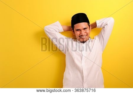 Relaxed Young Asian Muslim Man With A Blissful Smile Leaning Back, Isolated Over Yellow Color