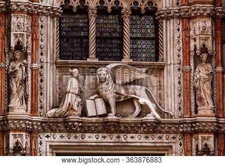 Venetian Lion And Saint Mark On The Pediment Of The Doge Palace. Venice, Italy.