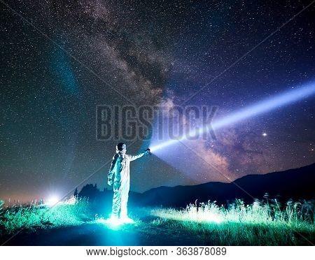 Full Length Of Astronaut Illuminating Beautiful Starry Sky With Flashlight. Cosmonaut Wearing White