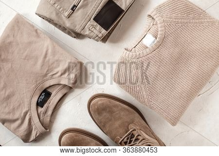 Group Of Fashionable Clothes On The Table. Beige Denim Pants, Cotton Shirt, Woolen Knitted Vintage S