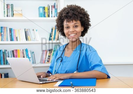 Laughing Afro American Nurse Or Medical Student At Computer At Hospital