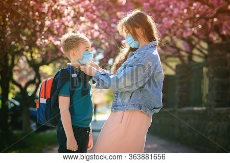 Schoolboy Is Ready Go To School. Mother Puts A Safety Mask On Her Son's Face. Back To School Concept