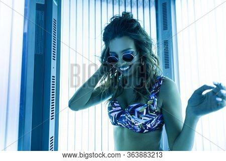 Beautiful Joyful Young Woman With Smile Is Sunbathing In A Solarium. Cheerful Glamorous Girl Model I