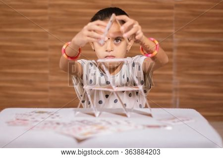 Young Girl Kid Busy In Building Pyramid With House Of Cards At Home - Concept Of Focus Or Concentrat