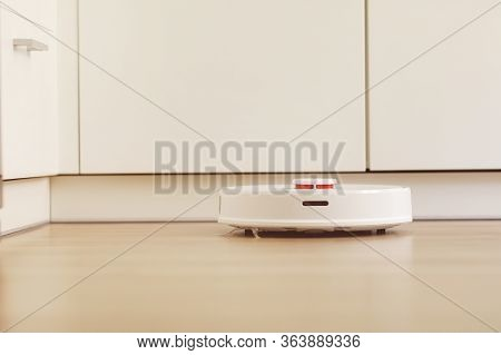 White Robot Vacuum Cleaner Cleans The Floor From Debris, Home Cleaning With An Electric Vacuum Clean