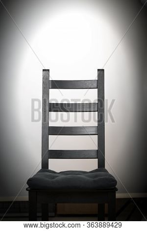 Empty Black Wooden Chair On White Background In Spotlight At Darkness. Prison, Scary, Mystical, Stra