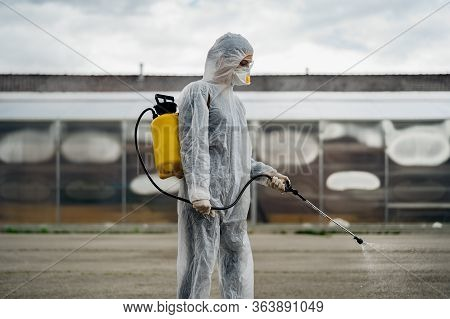 Sanitation Worker In Hazmat Protection Suit And N95 Mask With Chemical Decontamination Sprayer Tank.