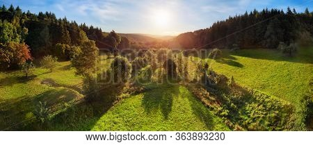 Aerial Landscape Panorama After Sunrise: Gorgeous Scenery With The Sun In The Blue Sky, Trees On Gre