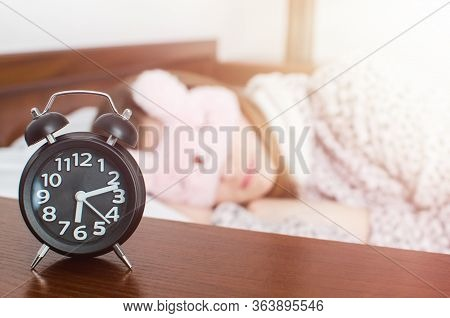 Young Woman Girl In Cute Sleep Mask And Warm Pajamas Sleep With Alarm Clock Near The Bed In The Morn